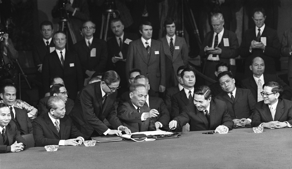 """. PARIS, FRANCE:  Photo taken 27 January 1973 in Paris, of US, South Vietnamese, North Vietnamese, and Viet Cong representatives signing the long-sought cease-fire agreement that ended the war in Viet-Nam. According to the 1st article of the peace agreement, the \""""United States and all other countries respect the independence, sovereignty, unity, and territorial integrity of Viet-Nam as recognized by the 1954 Geneva Agreements on Viet-Nam\"""". Was present North Vietman\'s Nguyen Duy Trinh (4thL). AFP PHOTO (Photo credit should read AFP/Getty Images)"""