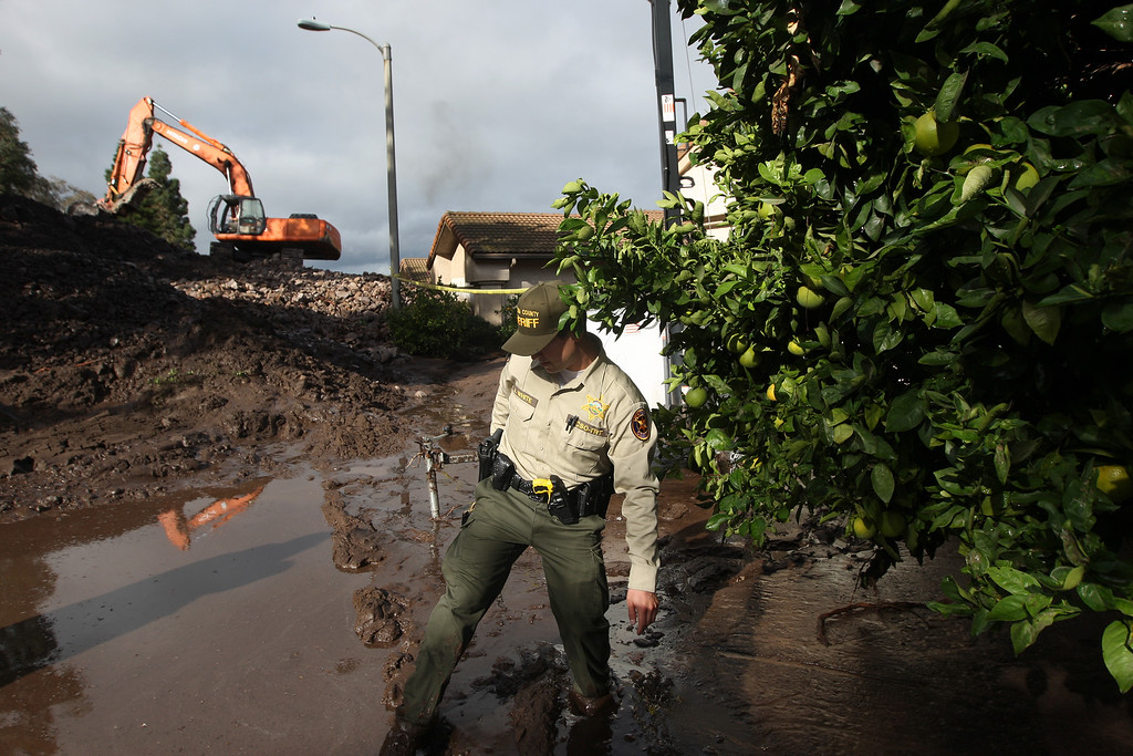 . A Ventura County Sheriffs deputy walks through mud and passes an orange tree as a backhoe clears a pile of rocks and mud after debris flows smashed into homes as a powerful storm that has been lashing northern California moves southward on December 12, 2014 in Camarillo Springs neighborhood of Camarilla, California.  (Photo by David McNew/Getty Images)
