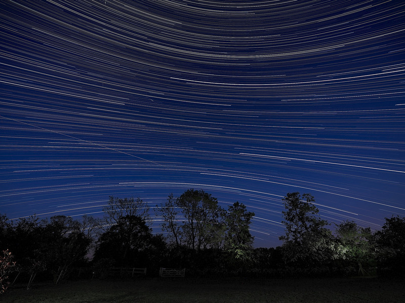 StarTrail 25/26 May 2014, Leicestershire, UK. Reverse curvature startrail captured with Olympus OM-D E-M1 & 7-14mm lens. If you look closely the image contains 1 Iridium flare, 4 meteors and the 0225hrs ISS flyby. A nice composite capture :-) How did I capture it? - Camera on tripod F4, ISO 320, 15s. Manual focus set to infinity I pointed the camera due south to ensure a star reversal curvature. The first shot was captured/exposed through the lcd screen and then using the remote cable (set to lock) and turning off lcd (maximise battery) I depressed shutter. This allowed the camera to shoot continuous for 5 hours.  To complete the process I transferred all images (High res JPEG) to MAC and imported/stacked in StarStax software. Plane trails removed using Pixelmator software. The final composite reveals stars reverse arcing above and below the celestial equator.