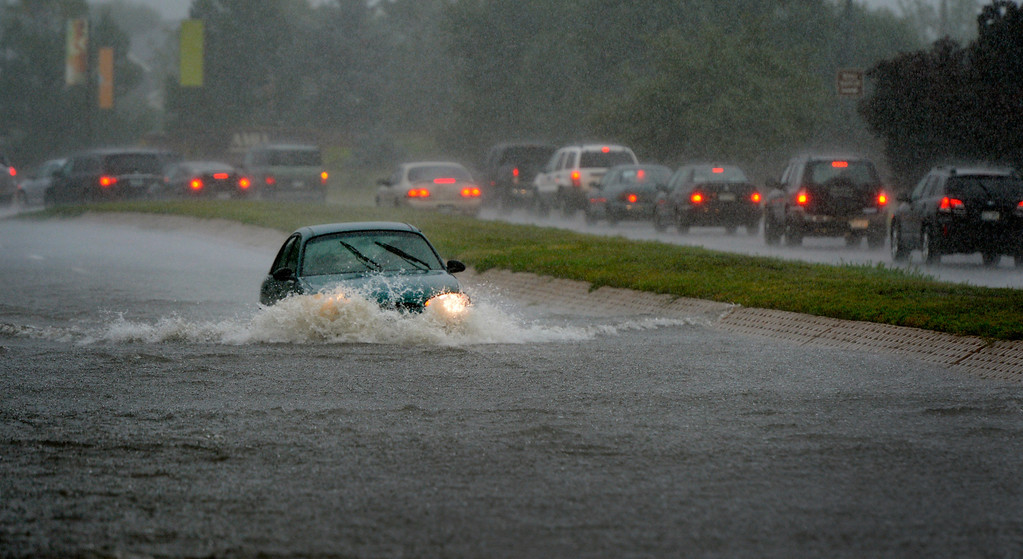 . AURORA, CO. - SEPTEMBER12:  A driver passes through a flooded section of Alameda Ave in Denver, CO September 12, 2013. Crews are working to clear drains and roads as standing water and weather conditions continue to cause problems in some areas across the city.(Photo By Craig F. Walker / The Denver Post)