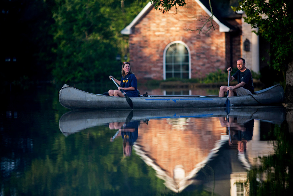 . Danny and Alys Messenger canoe away from their flooded home after reviewing the damage in Prairieville, La., Tuesday, Aug. 16, 2016.  As waters begin to recede in parts of Louisiana,  some residents struggled to return to flood-damaged homes on foot, in cars and by boat. (AP Photo/Max Becherer)