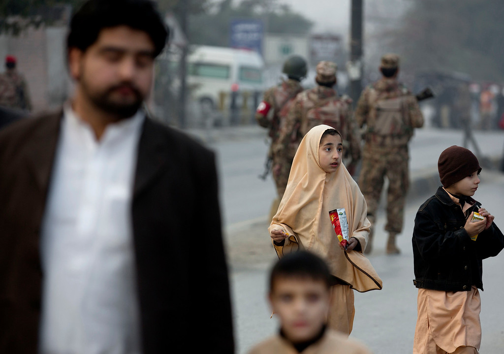 . A family member escorts children outside a school attacked by the Taliban in Peshawar, Pakistan, Tuesday, Dec. 16, 2014. Taliban gunmen stormed a military-run school in the northwestern Pakistani city of Peshawar on Tuesday, killing and wounding scores, officials said, in the highest-profile militant attack to hit the troubled region in months. (AP Photo/B.K. Bangash)