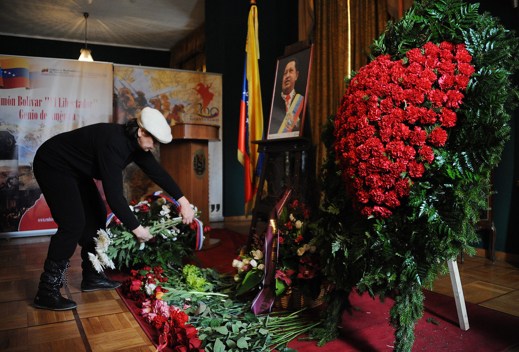 . A woman lays flowers a portrait of late Venezuelan President Hugo Chavez at the Venezuela\'s embassy in Moscow on March 6, 2013.  Russian President Vladimir Putin hailed today his late Venezuelan counterpart Hugo Chavez as an uncommon and strong man who had made a huge contribution to relations between Moscow and Caracas. Russia enjoys close military ties with Venezuela, which also represents one of the main oversees investment targets of the giant state oil company Rosneft. AFP PHOTO / NATALIA  KOLESNIKOVA/AFP/Getty Images