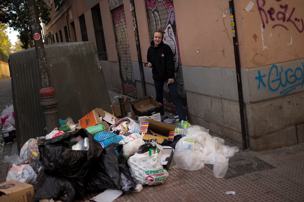 . A girl tries to avoid stepping on garbage as she walks down the street past containers already piled up with trash bags during the sixth day of a garbage collectors strike, in Madrid, Sunday, Nov. 10, 2013. Street cleaners and garbage collectors who work in the city\'s public parks walked off the job in a strike called by trade unions to contest the planned layoff of more than 1,000 workers. Madrid\'s municipal cleaning companies, which have service supply contracts with the city authorities, employ some 6,000 staff. (AP Photo/Daniel Ochoa de Olza)