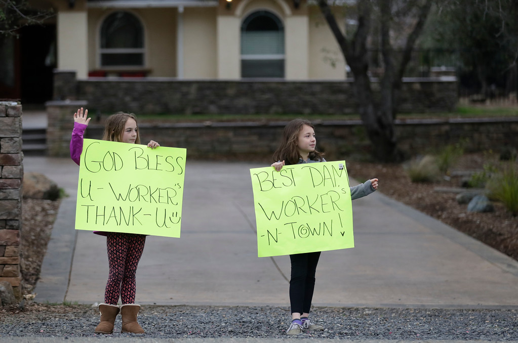 . Kylie Atteberry, left, 12, and her cousin McKena Harvey, 9, wave at passing work crews Wednesday, Feb. 15, 2017, in Oroville, Calif. The Oroville Reservoir is continuing to drain Wednesday as state water officials scrambled to reduce the lake\'s level ahead of impending storms. (AP Photo/Marcio Jose Sanchez)