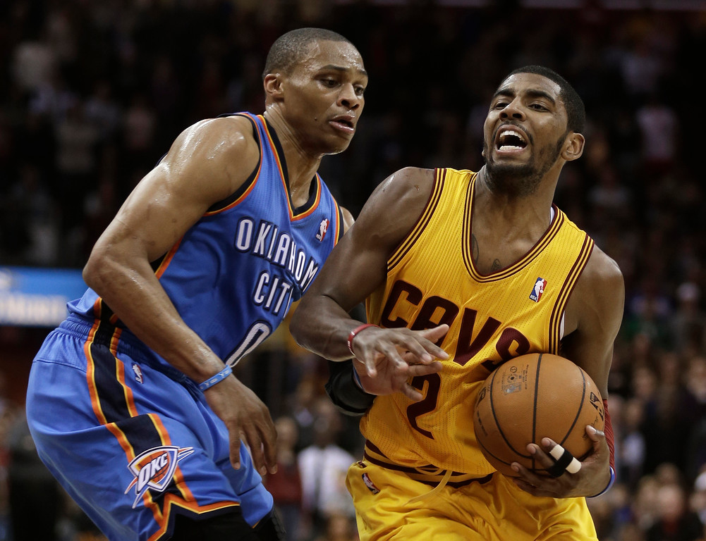 . Cleveland Cavaliers\' Kyrie Irving, right, drives to the basket against Oklahoma City Thunder\'s Russell Westbrook (0) during the fourth quarter of an NBA basketball game on Saturday, Feb. 2, 2013, in Cleveland. Irving scored a team-high 35 points for the Cavaliers\' 115-110 win. (AP Photo/Tony Dejak)