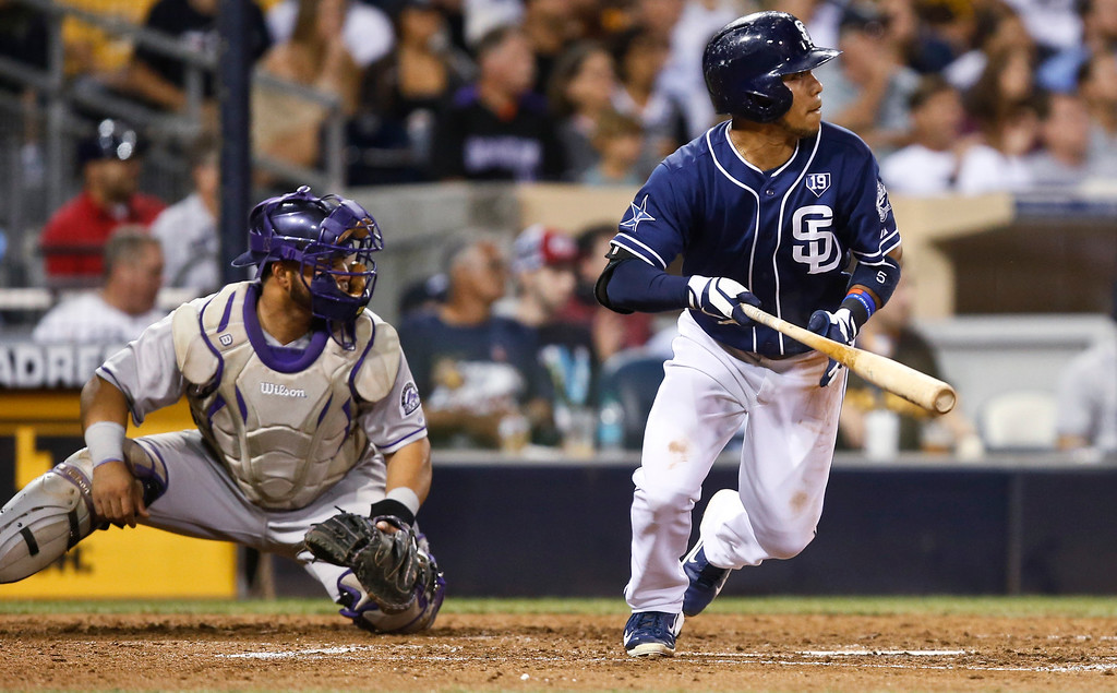 . San Diego Padres\' Alexi Amarista and Colorado Rockies catcher Wilin Rosario watch Amarista\'s soft line drive single head for left field in the sixth inning of a baseball game Tuesday, Sept. 23, 2014, in San Diego. (AP Photo/Lenny Ignelzi)