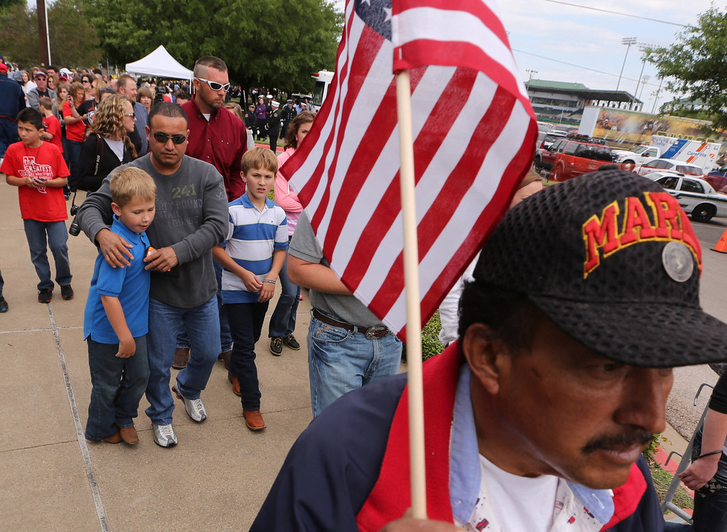 . Gulf war veteran Celso Castro, right carries an flag while heading to a memorial service for first responders who died in last week\'s fertilizer plant explosion in West, Texas, Thursday, April 25, 2013, in Waco, Texas. (AP Photo/Waco Tribune Herald, Rod Aydelotte)