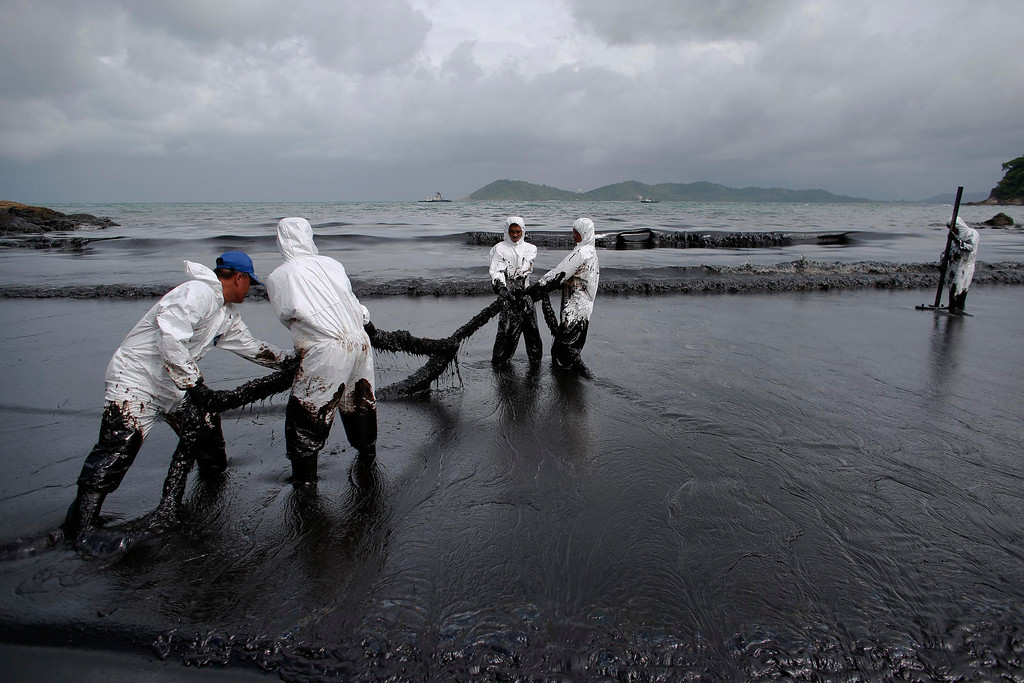 . Thai soldiers in white biohazard suits take part in a clean-up operation at Ao Prao Beach on Koh Samet, Rayong July 30, 2013. An oil spill that has blackened beaches at Koh Samet was having an extreme impact on tourism and could spread to the coast of the mainland and affect the fishing industry, officials and an environmental group said on Tuesday. REUTERS/Athit Perawongmetha