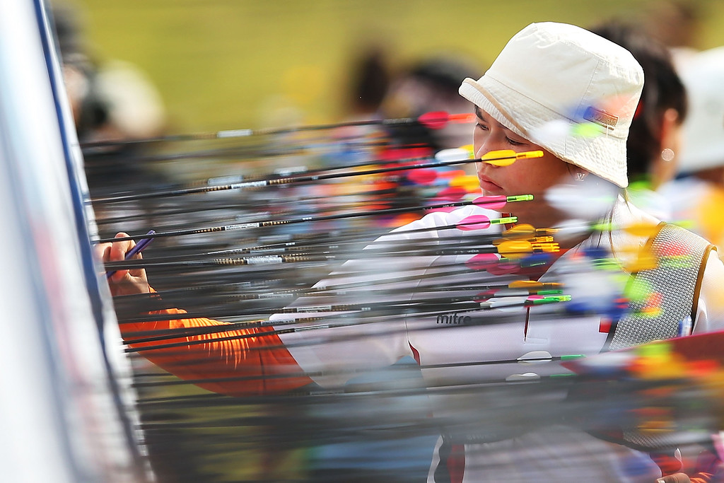 . Athletes pull out arrows from their targets in Women\'s 70m Recurve Qualification Round during day four of the 2014 Asian Games at Gyeyang Asiad Archery Field on September 23, 2014 in Incheon, South Korea.  (Photo by Brendon Thorne/Getty Images)