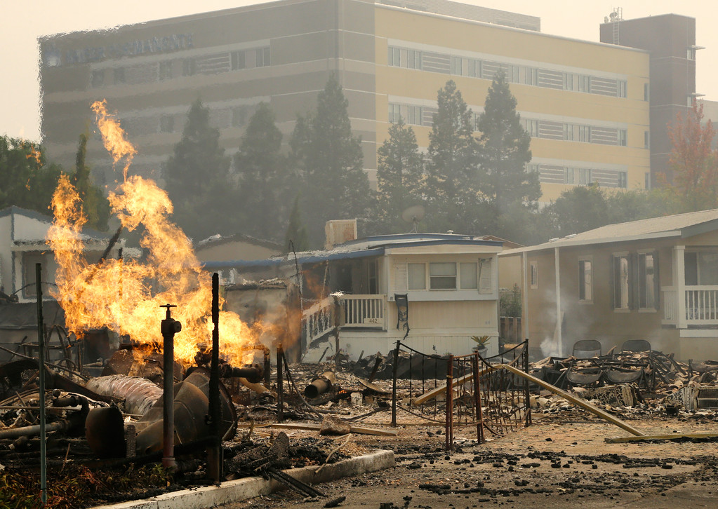. Flame from an open gas valve burns at the Journey\'s End mobile home park on Monday, Oct. 9, 2017, in Santa Rosa, Calif. Wildfires whipped by powerful winds swept through Northern California, sending residents on a headlong flight to safety through smoke and flames as homes burned. (AP Photo/Ben Margot)