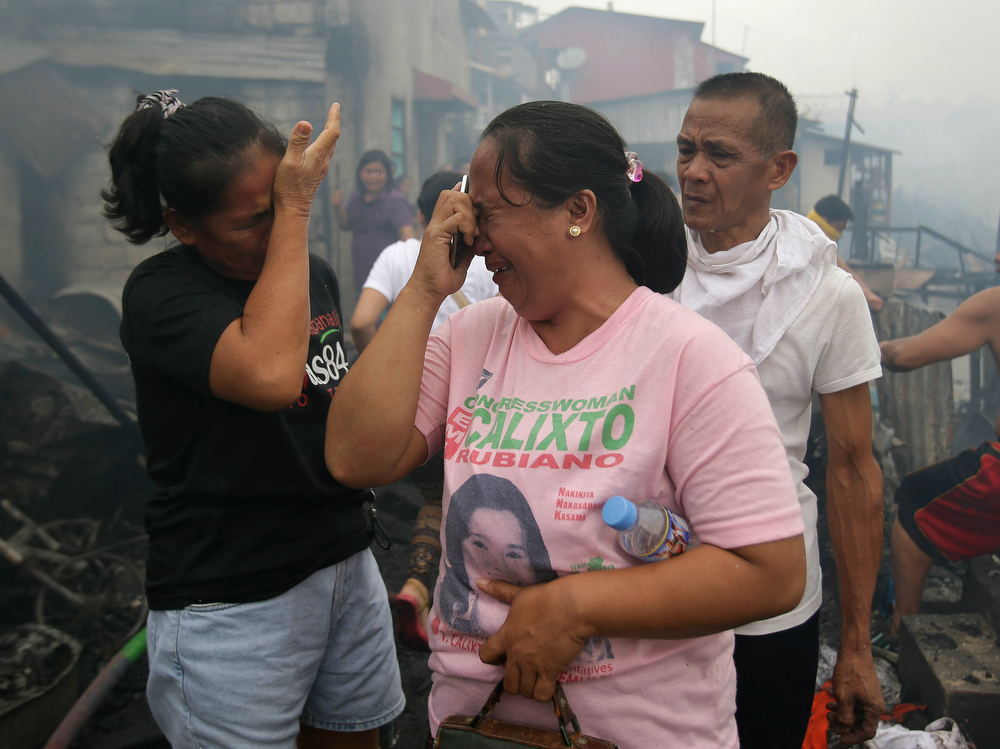 . Residents grieve as they check what remains of their homes after a fire broke out at a slum area in Pasay, south of Manila, Philippines on Wednesday, July 24, 2013. Pasay City Fire Marshall Major Douglas Guiyab said about 250 houses were gutted in the area and the cause of the fire is still being determined. (AP Photo/Aaron Favila)