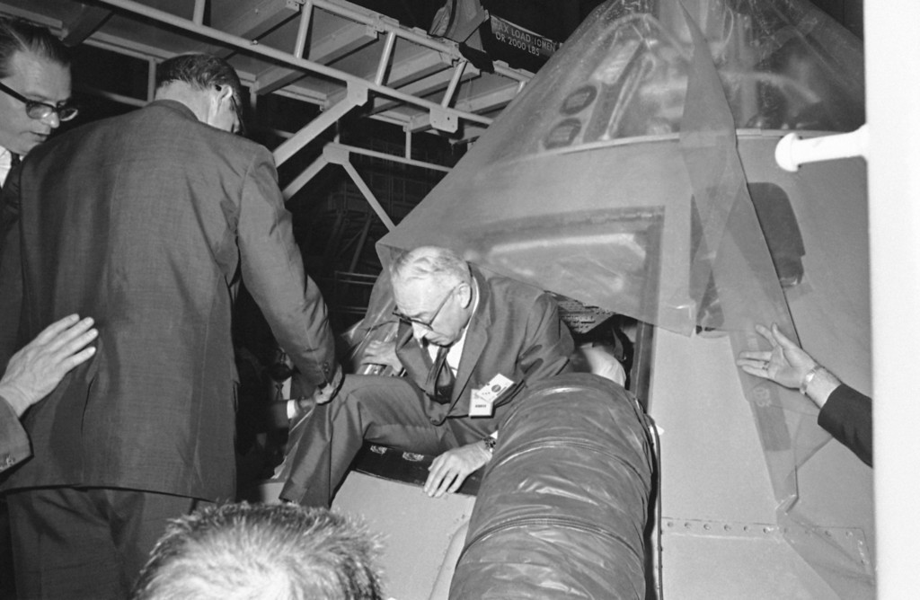 . Rep. Ken Hechler, D-W.Va., crawls from a spacecraft, a sister ship of Apollo 1, after entering for a briefing from Astronaut Frank Borman at Cape Kennedy, Florida on April 21, 1967. Rep. Hechler was a member of the House Sub-Committee on NASA oversight who was holding hearings at the Space Center on the Apollo 1 fire that killed astronauts Virgil I. Grissom, Edward H. White and Roger B. Chaffee. (AP Photo/Jim Kerlin/Pool)