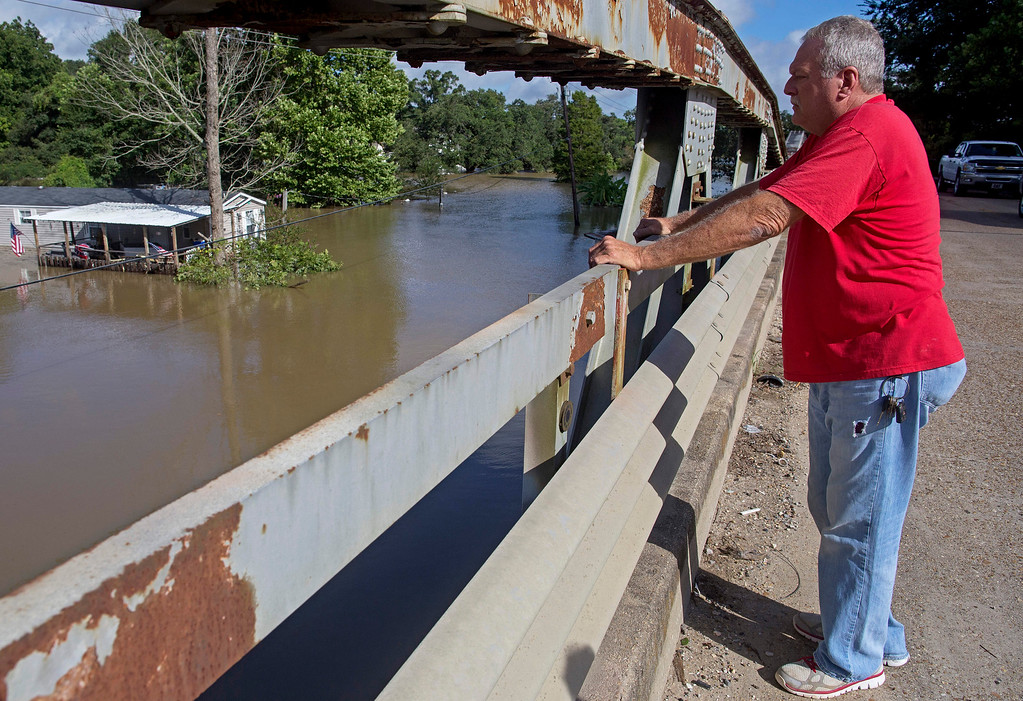 . National Weather Service cooperative observer Pokey Delaroderie observes flood water from a bridge on Old Jefferson Highway at Bayou Manchac in Prairieville, La., Tuesday, Aug. 16, 2016. Rivers and creeks were still dangerously bloated in areas south of Baton Rouge as people filled sandbags there to protect their houses, bracing for the worst as the water worked its way south. In one area, Ascension Parish, officials said some small towns have already been inundated.  (AP Photo/Max Becherer)
