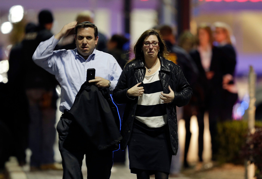 . A man and woman leave the Garden State Plaza Mall with officials standing guard behind them following reports of a shooter, Monday, Nov. 4, 2013, in Paramus, N.J. Hundreds of law enforcement officers converged on the mall Monday night after witnesses said multiple shots were fired there. (AP Photo/Julio Cortez)