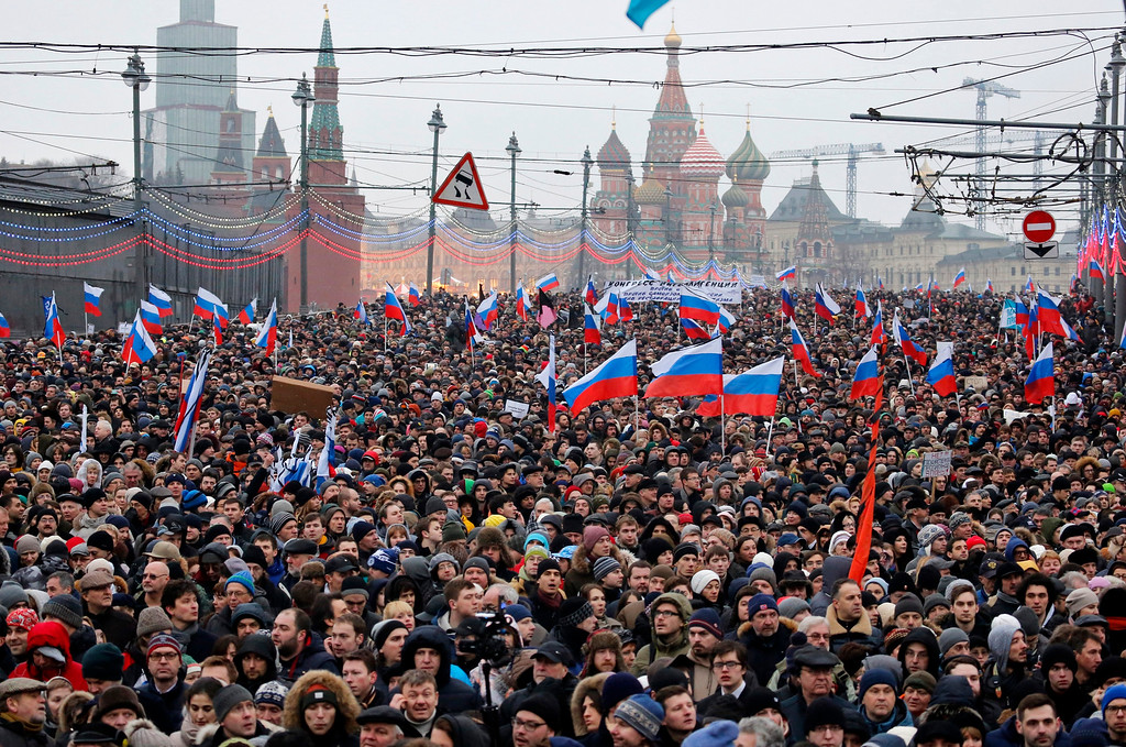 . People carry Russian national flags during a march in memory of opposition leader Boris Nemtsov who was gunned down on Friday, Feb. 27, near the Kremlin, with The Kremlin Wall and St. Basil Cathedral in the background,  in Moscow, Russia, Sunday, March 1, 2015. Thousands converged Sunday in central Moscow to mourn veteran liberal politician Boris Nemtsov, whose killing on the streets of the capital has shaken Russiaís beleaguered opposition. (AP Photo/Dmitry Lovetsky)