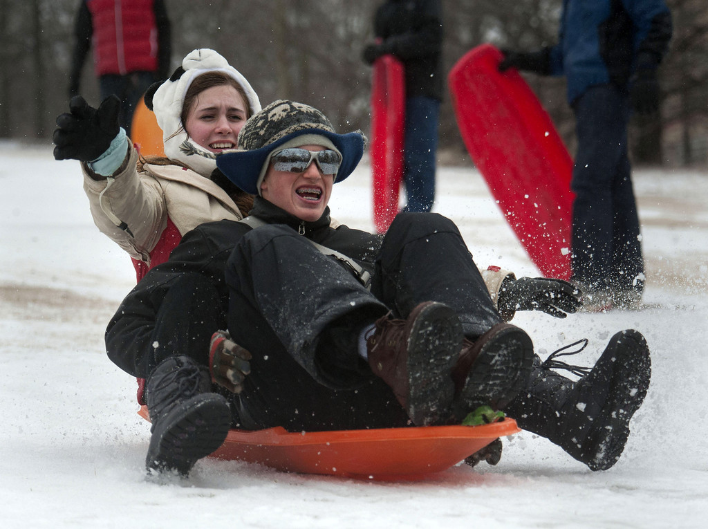 . Hank Persons and Grace Hawkins sled down a hill at Candler Park on February 12, 2014 in Atlanta, Georgia. Public schools were closed for another day, and hazardous road conditions kept most people home. A state of emergency was declared in 45 Georgia counties as sleet, freezing rain and snow fell across the state. (Photo by Davis Turner/Getty Images)