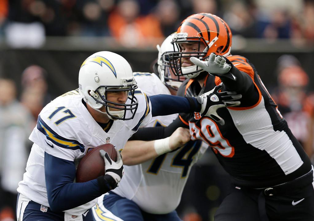 . San Diego Chargers quarterback Philip Rivers (17) runs against Cincinnati Bengals defensive end Margus Hunt in the first half of an NFL wild-card playoff football game on Sunday, Jan. 5, 2014, in Cincinnati. (AP Photo/Al Behrman)