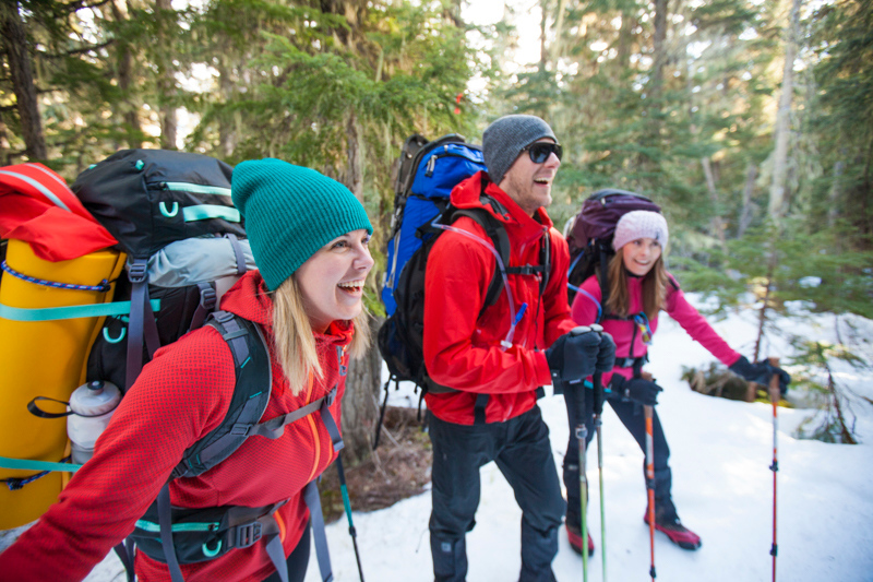Three backpackers share a laugh while hiking.