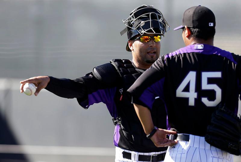 . Colorado Rockies\' Yorvit Torrealba, left, talks with Jhoulys Chacin during a spring training baseball workout Tuesday, Feb. 12, 2013, in Scottsdale, Ariz. (AP Photo/Darron Cummings)