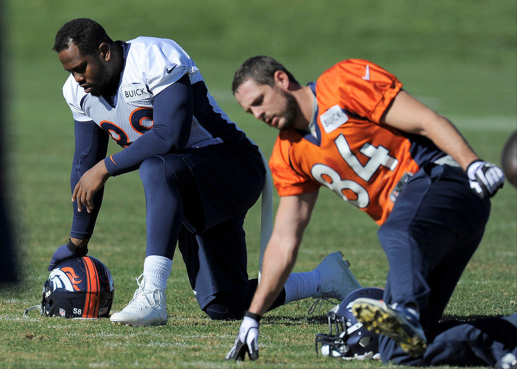 . Denver Broncos Von Miller (58) and Jacob Tamme (84) stretch during practice on October 30, 2013 at Dove Valley. Von Miller wore Demaryius Thomas jersey as the players swapped jerseys for Halloween. (Photo by John Leyba/The Denver Post)