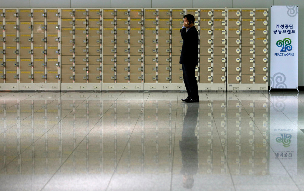 . A South Korean man uses his mobile phone in front of empty lockers which are used for worker\'s belongings before leaving for the North Korean city of Kaesong, at the customs, immigration and quarantine office near the border village of Panmunjom, that has separated the two Koreas since the Korean War, in Paju, north of Seoul, South Korea, Monday, April 8, 2013. North Korea raised tensions Wednesday when it barred South Koreans and supply trucks from entering the Kaesong industrial complex, where South Korean companies have employed thousands of North Korean workers for the past decade.   (AP Photo/Lee Jin-man)
