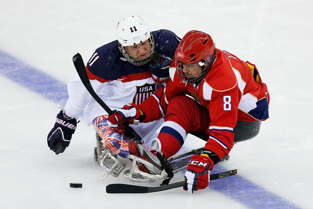 . Dmitrii Lisov of Russia (R) collides with Tyler Carron of USA during the Ice Sledge Hockey Gold Medal match between Russia and USA at the Shayba Arena during day eight of the 2014 Paralympic Winter Games on March 15, 2014 in Sochi, Russia.  (Photo by Harry Engels/Getty Images)
