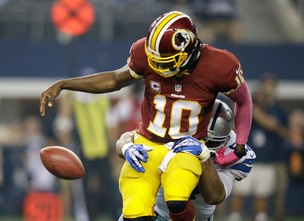 . Washington Redskins quarterback Robert Griffin III (10) loses the ball after being sacked by Dallas Cowboys defensive tackle Jason Hatcher in the second half of an NFL football game, Sunday, Oct. 13, 2013, in Arlington, Texas. The Redskins recovered the fumble.  (AP Photo/Tim Sharp)
