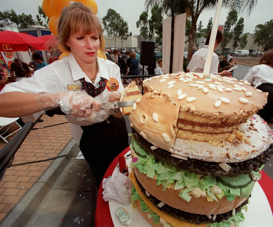 ". Lucy Patton cuts a giant cake in the shape of a Big Mac hamburger as part of festivities celebrating the 30th anniversary of McDonald\'s ""flagship\"" sandwich at the restaurant chain\'s outlet in Irwindale, Calif., Wednesday, Sept. 9, 1998.  A September promotion will celebrate the anniversary by rolling back prices to 1968 levels and introducing new items in an effort to bring back old and new customers who have drifted away from the menu. (AP Photo/Reed Saxon)"