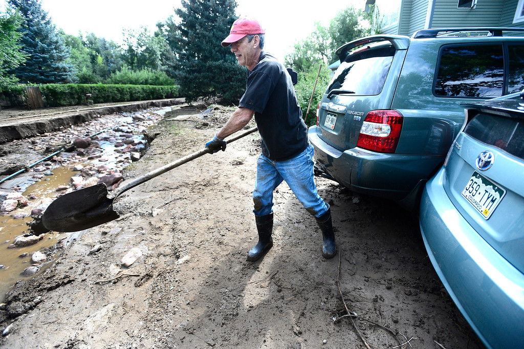 . Jeff Kless dumps a shovel full of dirt a washed out Topaz Drive in Boulder on Saturday.  Kless was trying to separate his family\'s two cars which were smashed together by flood waters.  Photo by Paul Aiken / The Daily Camera / Saturday September 14, 2013