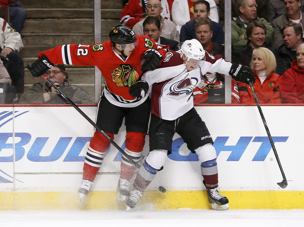 . Chicago Blackhawks center Peter Regin (12) checks Colorado Avalanche defenseman Tyson Barrie (4) along the boards during the first period of an NHL hockey game Tuesday, March 4, 2014, in Chicago. (AP Photo/Charles Rex Arbogast)