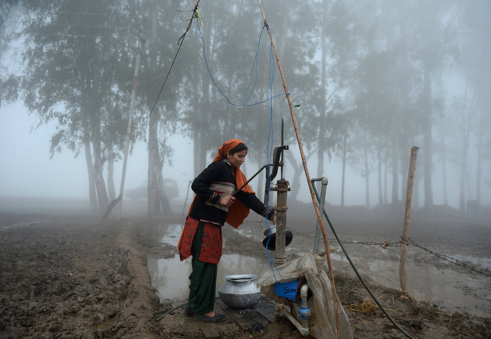 Description of . An Indian woman uses a handpump to  during a dense fog along the India-Pakistan border in Suchit-Garh, 36 kms southwest of Jammu on January 10, 2013.   The beheading of an Indian soldier may have sparked a war of words between Delhi and Islamabad but the two nuclear rivals are both determined to prevent it from wrecking a fragile peace process.  Two Indian soldiers died after a firefight erupted in disputed Kashmir on Tuesday as a patrol moving in fog discovered Pakistani troops about 500 metres (yards) inside Indian territory, according to the Indian army.  TAUSEEF MUSTAFA/AFP/Getty Images