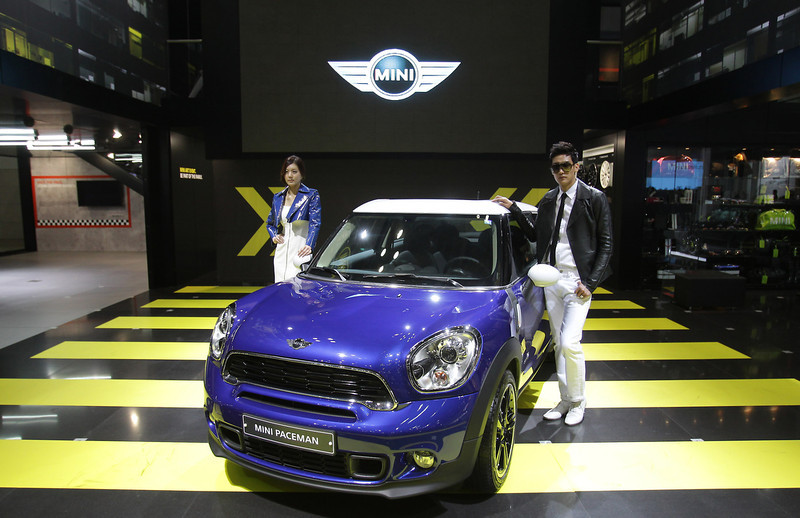. Models pose next to a MINI Paceman at the Seoul Motor Show 2013 on March 28, 2013 in Goyang, South Korea. The Seoul Motor Show 2013 will be held in March 29-April 7, featuring state-of-the-art technologies and concept cars from global automakers. The show is its ninth since the first one was held in 1995. About 384 companies from 14 countries, including auto parts manufacturers and tire makers, will set up booths to showcase trends in their respective industries, and to promote their latest products during the show.  (Photo by Chung Sung-Jun/Getty Images)