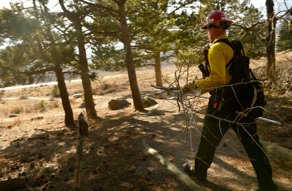 . Wildland firefighter Mark Murray, from Lafayette Fire, clears brush and debris from the Moraine Park Vistor\'s Center to protect the structure just in case the fire reaches the building on December 2nd, 2012.