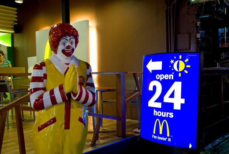Ronald McDonald next to 24-hour sign in McDonald's Phuket branch