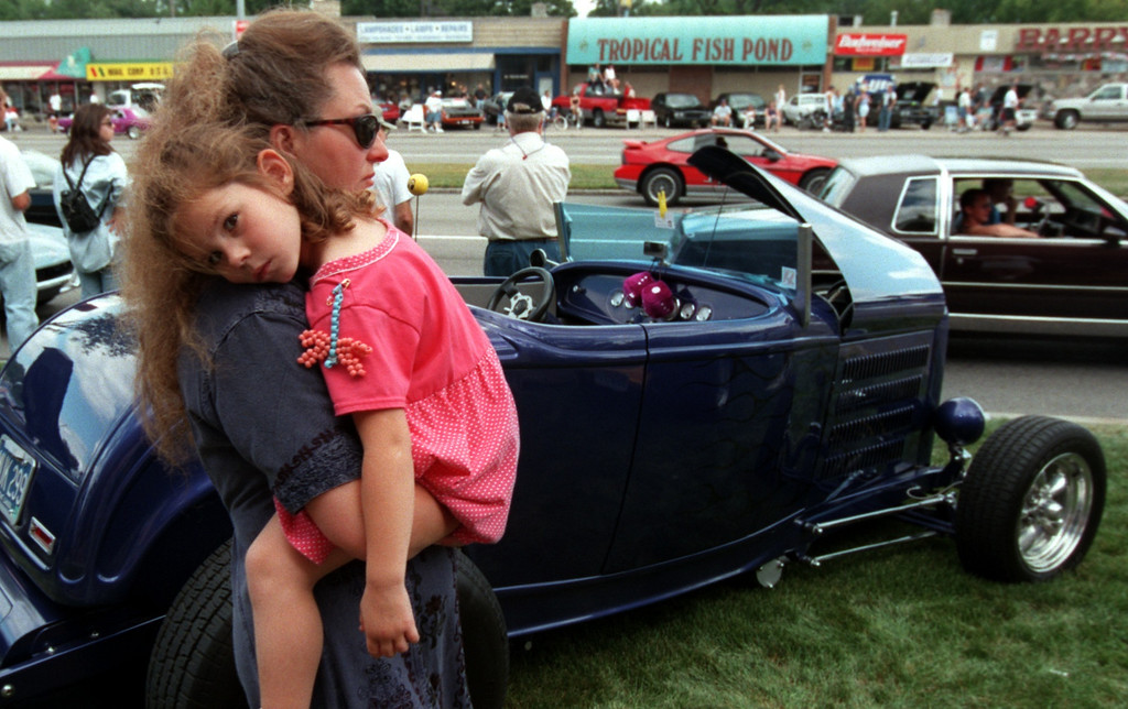 . Joanne Saber of Lake Orion holds her granddaughter Ashley Saber,5,  as they look at classic cars along Woodward Ave. during the Fifth Annual Woodward Dream Cruise.