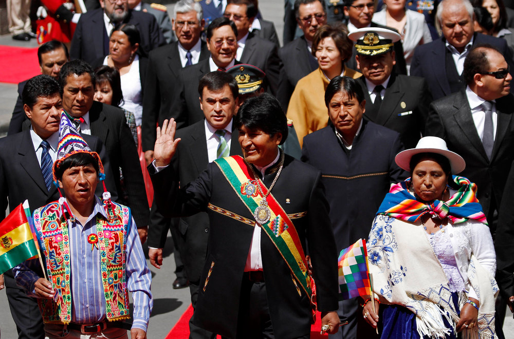 Description of . Bolivia's President Evo Morales, center, waves to supporters as he arrives to the National Congress, flanked by lawmakers and ministers, to deliver his state of the nation speech in La Paz, Bolivia, Tuesday, Jan. 22, 2013. Morales is marking his seventh year as president. (AP Photo/Juan Karita)