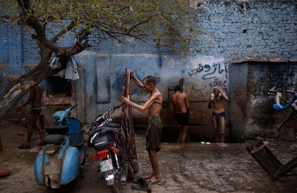 . Pakistani Kushti wrestlers, right, shower after attending their training at a wrestling club in Lahore, Pakistan, Tuesday, Feb. 26, 2013. Kushti, an ancient Indo-Pakistani form of wrestling, is several thousand years old and is a national sport in Pakistan. (AP Photo/Muhammed Muheisen)