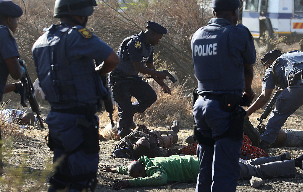 . In this Aug. 16, 2012 file photo, police surround the bodies of striking miners after opening fire on a crowd at the Lonmin Platinum Mine near Rustenburg, South Africa. South African police opened fire on a crowd of striking workers at a platinum mine, leaving an unknown number of people injured and possibly dead. Motionless bodies lay on the ground in pools of blood.  (AP Photo/File)