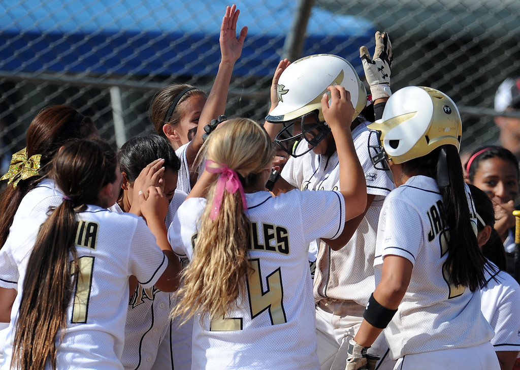 . Northview\'s Jocelyn Marquez, center, is mobbed by teammates after hitting a solo home run in the sixth inning of a CIF-SS quarterfinal playoff softball game against Barstow at Northview High School on Thursday, May 23, 2013 in Covina, Calif. Northview won 5-4.  (Keith Birmingham Pasadena Star-News)