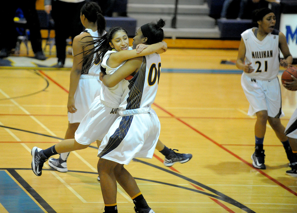 . 02-16-2012--(LANG Staff Photo by Sean Hiller)- Alex Saldana jumps into the arms of Dionna Henley after Millikan beat Rancho Cucamonga 73-19 in Saturday night\'s  first-round CIF girls basketball game at Millikan High School in Long Beach.