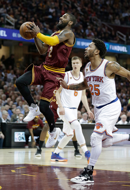 . Cleveland Cavaliers\' Kyrie Irving (2) drives to the basket against New York Knicks\' Derrick Rose (25) in the first half of an NBA basketball game, Thursday, Feb. 23, 2017, in Cleveland. (AP Photo/Tony Dejak)