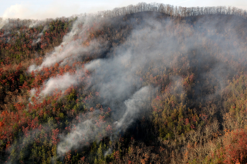. Wildfires burn Tuesday, Nov. 29, 2016, near Gatlinburg, Tenn. Thousands of people have fled wildfires that killed at least three people and destroyed hundreds of homes and a resort in the Great Smoky Mountains. (AP Photo/Wade Payne)