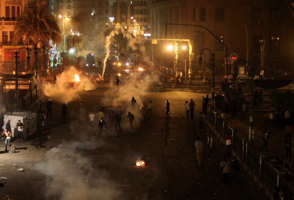 . Tear gas fills downtown as protesters clash with security forces in downtown Cairo, Egypt, Saturday, April 6, 2013. Police fired tear gas at hundreds of protesters outside the chief prosecutor\'s office Saturday in central Cairo who were pushing on the building\'s doors demanding he resign.(AP Photo/Mostafa Elshemy)