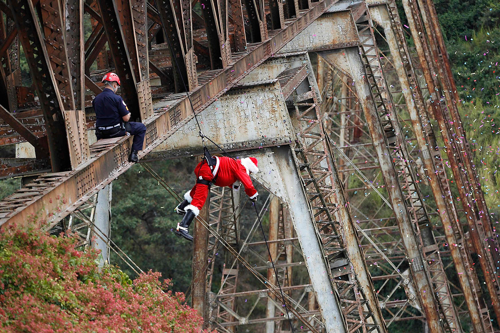 Description of . Guatemalan firefighter Hector Chacon, dressed as Santa Claus, rappels down from the Belize bridge to give toys to children living in the area under the bridge, a very poor area of Guatemala City, on December 23, 2012. The Guatemalan firefighters have been giving toys to the children living in the neighborhoods under the Belize bridge dressed as Santa Claus for 15 years. REUTERS/Jorge Dan Lopez