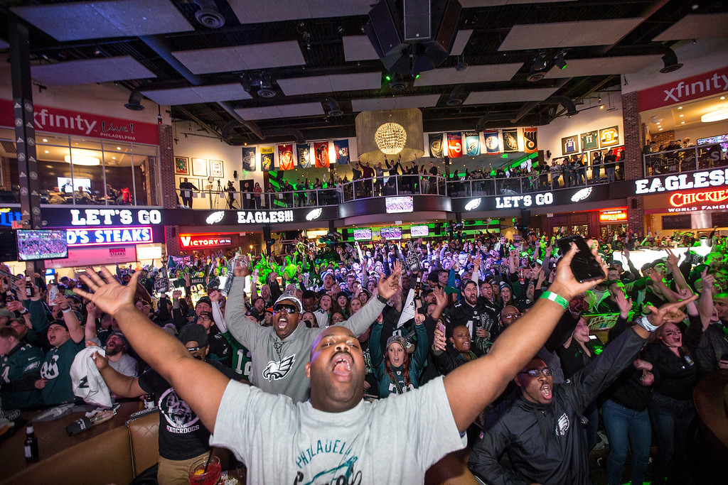 . Dan Smith, center, and other fans celebrate at a Super Bowl party at Xfinity Live! in Philadelphia as the Philadelphia Eagles were taking an early lead over the New England Patriots in the NFL Super Bowl 52 football game on Sunday, Feb. 4, 2018. The Eagles won 41-33. (Charles Fox/The Philadelphia Inquirer via AP)