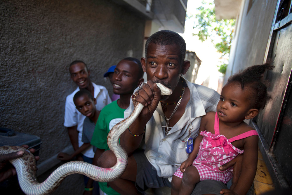 . In this Jan. 27, 2013 photo, a man kisses a snake for good luck after paying snake handler Saintilus Resilus performing in the street during the pre-Lenten Carnival season in Petionville, Haiti. It\'s the serpents that help Resilus eat and pay rent, in addition to his work for a neighborhood herbologist. And it\'s the snakes for which he\'s most famous. (AP Photo/Dieu Nalio Chery)