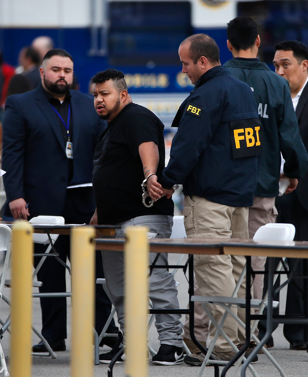 . A man is taken into custody by an FBI agent Wednesday, May 17, 2017, in Los Angeles. Hundreds of federal and local law enforcement fanned out across Los Angeles, serving arrest and search warrants as part of a three-year investigation into the violent and brutal street gang MS-13. (AP Photo/Jae C. Hong)