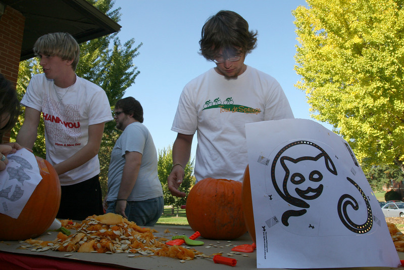Justus Hawks (senior, right) concentrates on his carving while Cam Mitchell (sophomore) guts his pumpkin.  Several students enjoy a pumpkin carving contest sponsored by SGA Thursday afternoon as part of the 2009 Homecoming festivities.