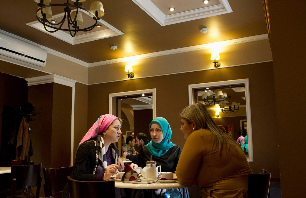 . Chechen women chat in a cafe in the centre of the Chechen capital Grozny April 23, 2013. The naming of two Chechens, Dzhokhar and Tamerlan Tsarnaev, as suspects in the Boston Marathon bombings has put Chechnya - the former site of a bloody separatist insurgency - back on the world\'s front pages. Chechnya appears almost miraculously reborn. The streets have been rebuilt. Walls riddled with bullet holes are long gone. New high rise buildings soar into the sky. Spotless playgrounds are packed with children. A giant marble mosque glimmers in the night. Yet, scratch the surface and the miracle is less impressive than it seems. Behind closed doors, people speak of a warped and oppressive place, run by a Kremlin-imposed leader through fear.   Picture taken April 23, 2013.   REUTERS/Maxim Shemetov